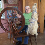Heandweaver Peggy Church spinning flax in her home studio.